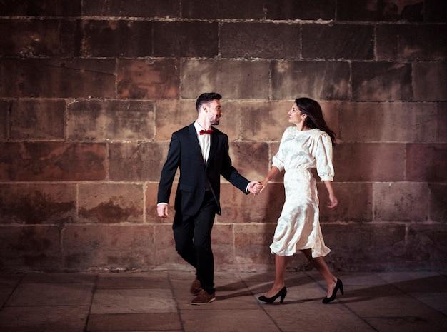 Мужчина в черном костюме танцует с женщиной на улице