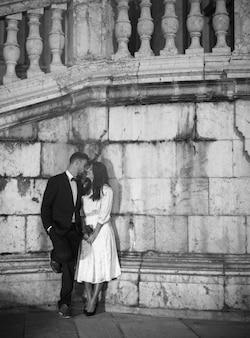 壁に傾いている通りでキスをするカップル