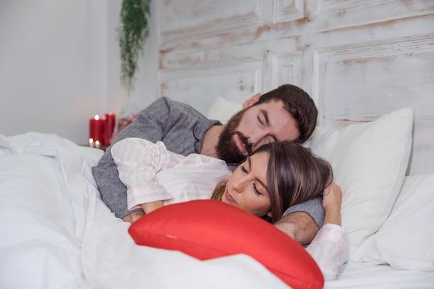ベッドで眠っている若いカップル