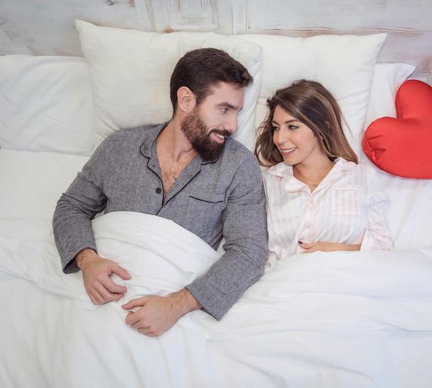 ベッドに横たわっているパジャマの若いカップル