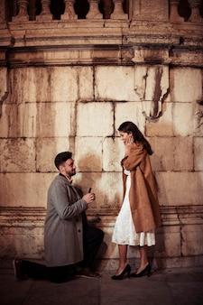 Мужчина делает предложение молодой женщине на улице