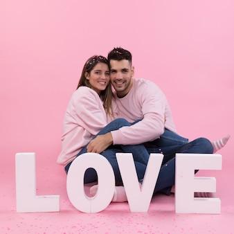 大きな愛のサインと色とりどりの近くに座っている若い笑顔のカップル