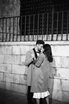 若い、幸せな男と抱きしめて手をつないでいるエレガントで陽気な女性