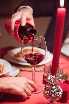 お祝いのテーブルでガラスにワインを注ぐ男