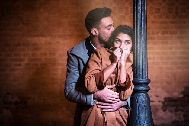 Молодой человек обнимает женщину возле уличного фонаря