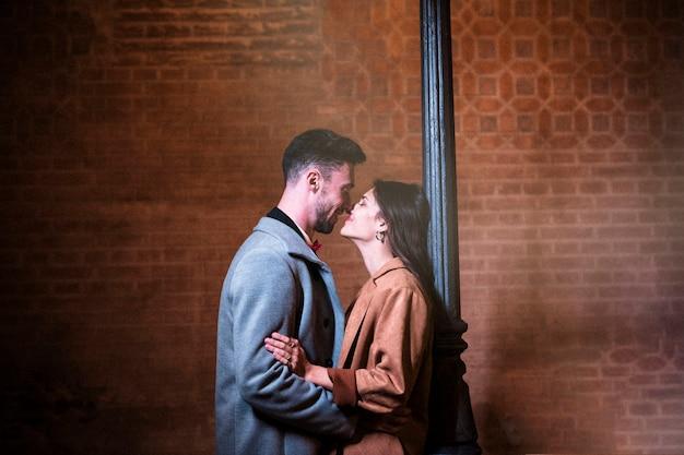 Молодой человек обнимает счастливую женщину возле уличного фонаря