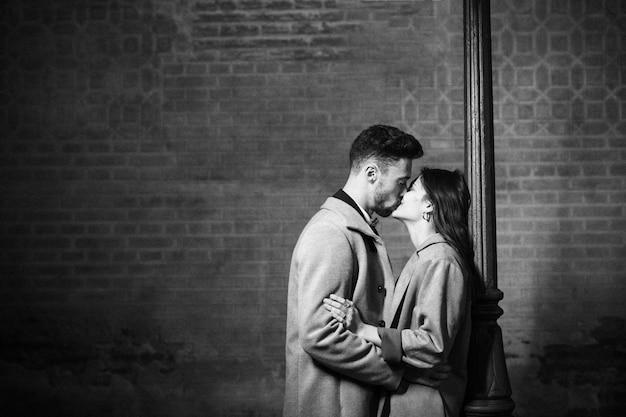 Молодой человек целует и обнимает женщину возле уличного фонаря