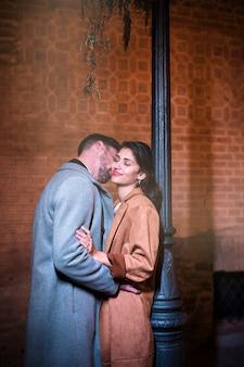 Молодой человек целует счастливую женщину возле уличного фонаря