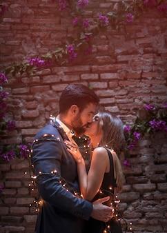 Молодая пара целуется в гирлянду