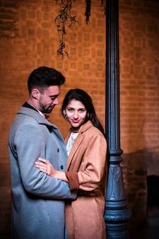 Молодой человек обнимает привлекательную счастливую женщину возле уличного фонаря
