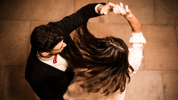 Молодой парень держит руку кружащейся элегантной леди