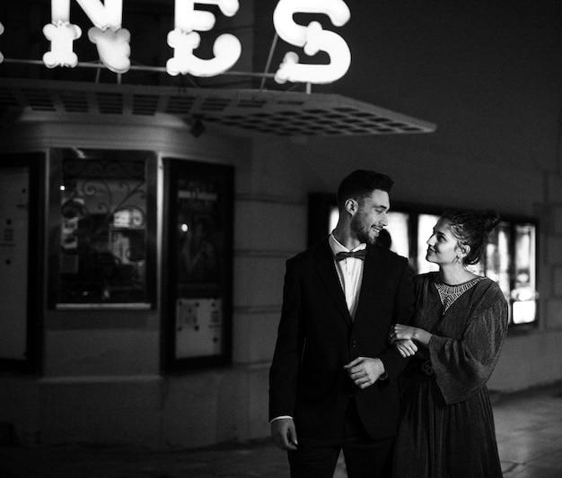 ストリートに若いポジティブな男と歩く魅力的な幸せな女性