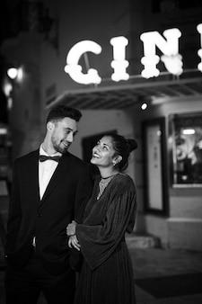 ストリートで若いポジティブな男と歩く魅力的な美しい幸せな女性