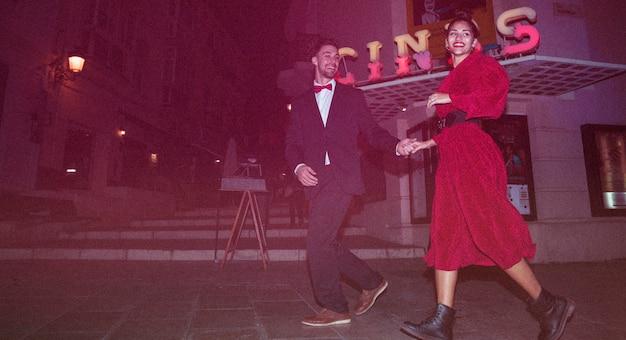 夕方に通りに若いポジティブな男と歩く美しい笑顔の女性