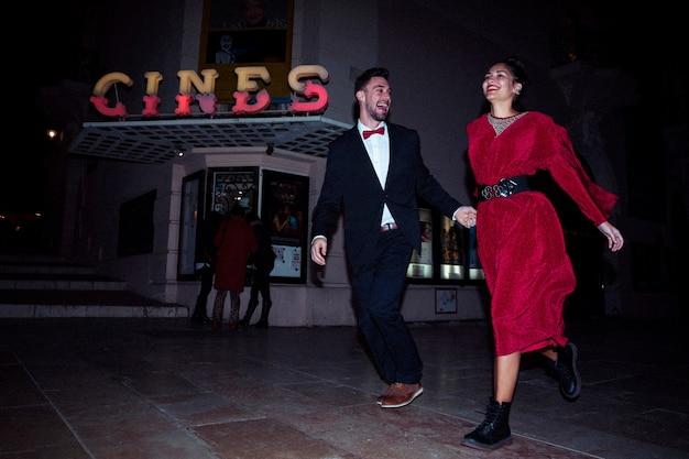 夕方に通りに若いポジティブな男と一緒に走っている美しい笑顔の女性