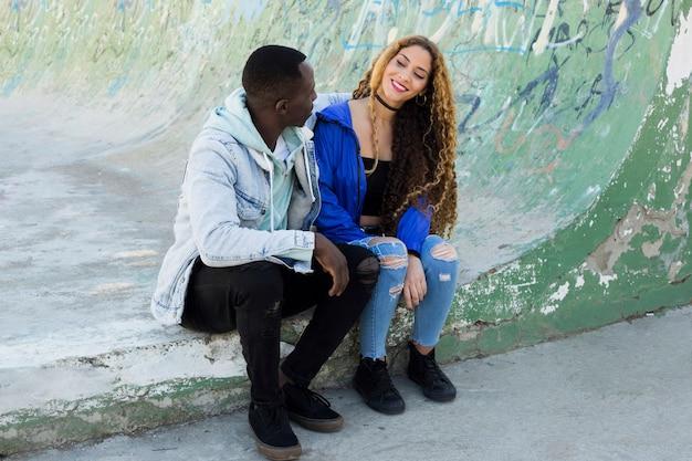 ハーフパイプに座っているアフロアメリカ人カップル