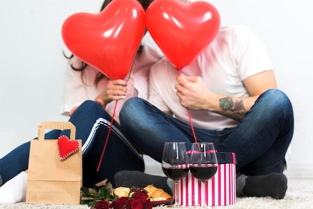 赤い心の風船で顔を覆うカップル