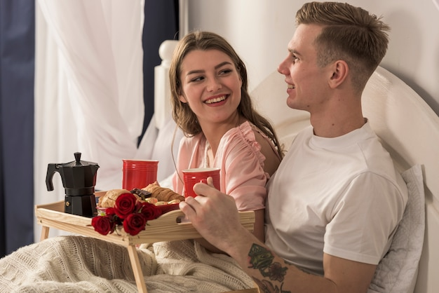 ベッドで朝食をする若いカップル