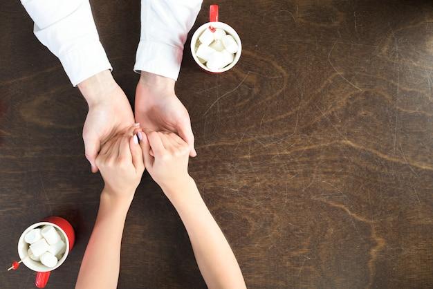 Молодая пара за столом с чашками, держась за руки