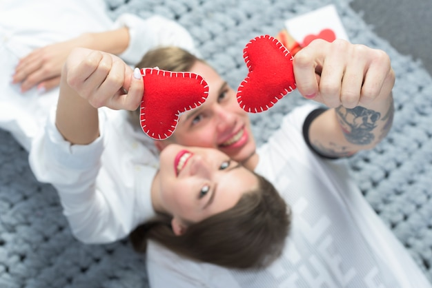 Пара держит в руках красные игрушечные сердечки