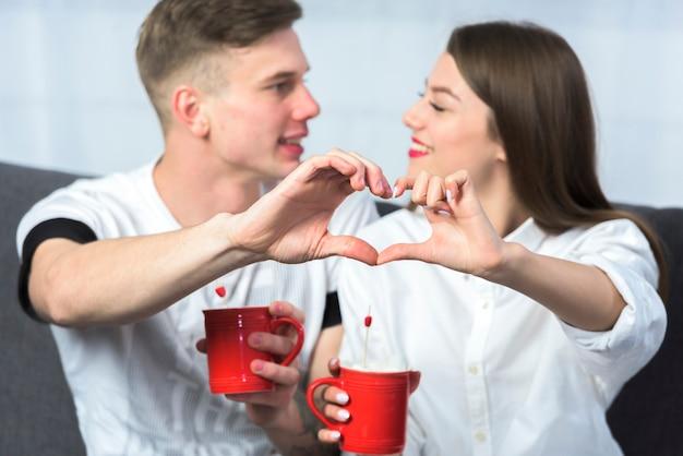 手で心臓の形を作るカップル