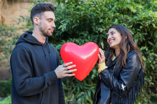 Молодой человек и улыбающаяся женщина с воздушным шаром в форме сердца