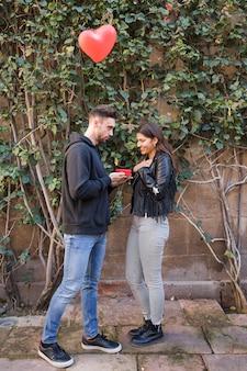 心臓の形で飛行バルーンの近くに驚いた女性にギフトボックスを提示する若い男