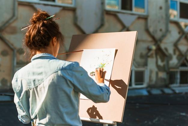 Женщина рисует на открытом воздухе