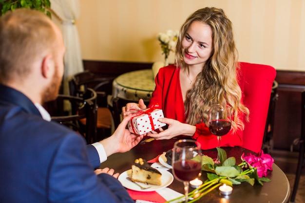 レストランでのテーブルで女性にギフトボックスを与える若い男