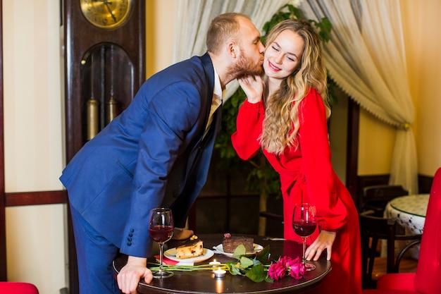 テーブルの上の頬に女にキスするスーツの男