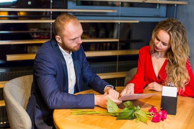 若いカップル、レストランで読書する