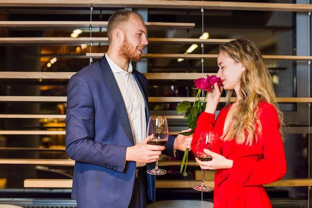 ワイングラスで女性にバラの花束を与える若い男
