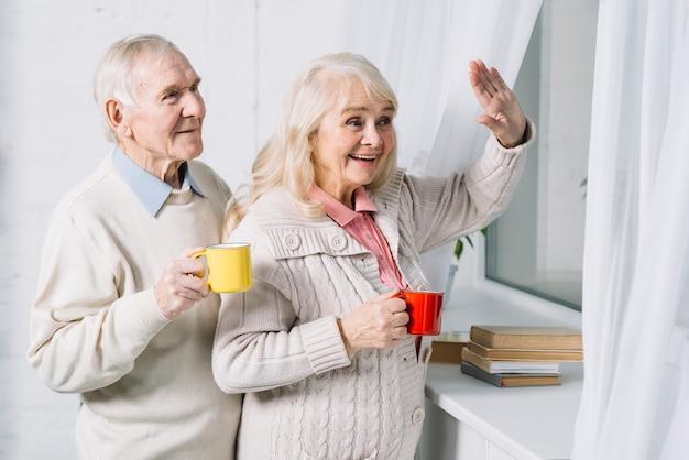 Пожилая пара говорит привет