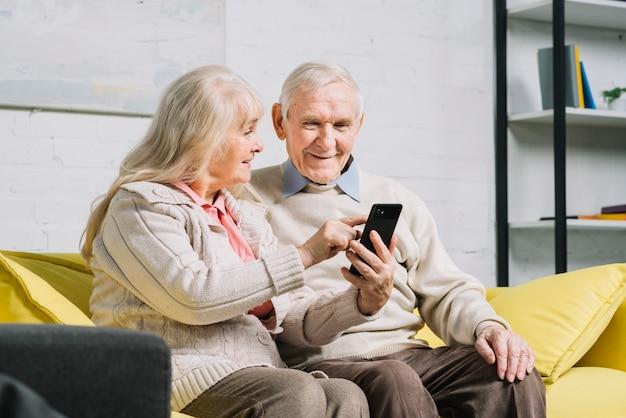 シニアのカップルがスマートフォンを使用