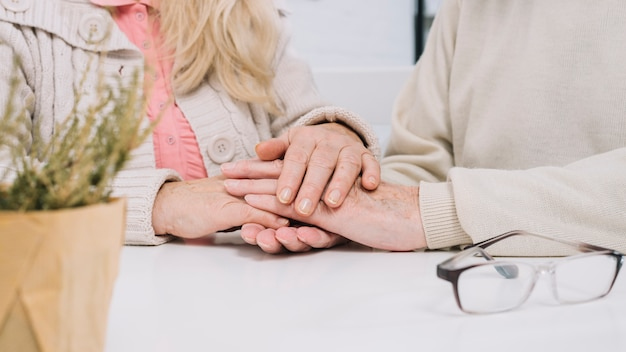 Пожилая пара за столом, держась за руки