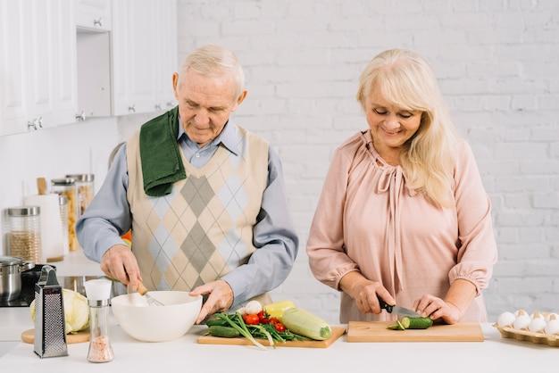 Пожилая пара готовит еду на кухне