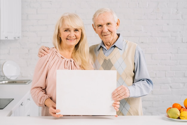 Пожилая пара держит шаблон в кухне