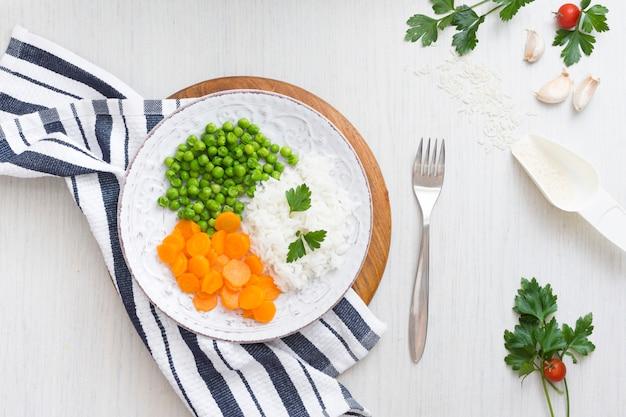 ナプキンとフォークの近くの木の板に野菜とご飯