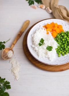 スプーンの近くの木の板に野菜添えご飯