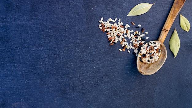 青いテーブルの上の木のスプーンでさまざまな米粒