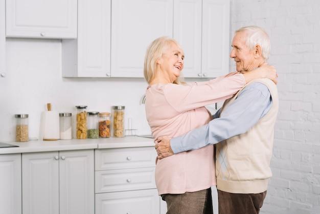 Пожилая пара танцует на кухне