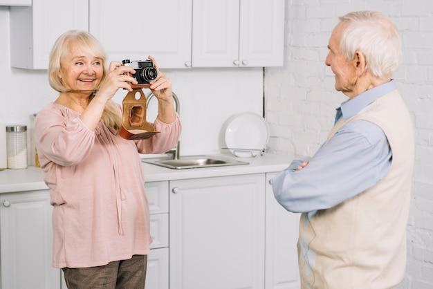 Пожилые супружеские пары, принимая фото в кухне
