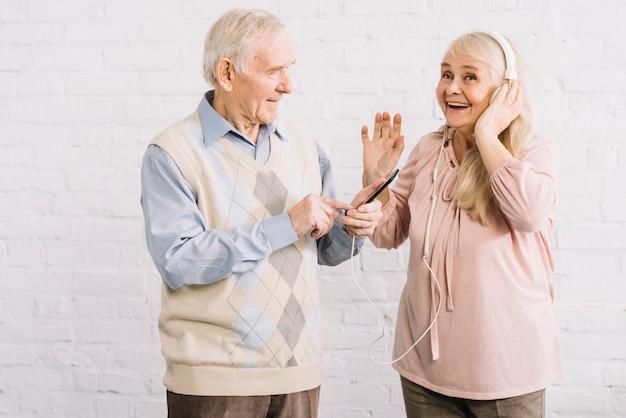 Пожилая пара слушает музыку на смартфоне