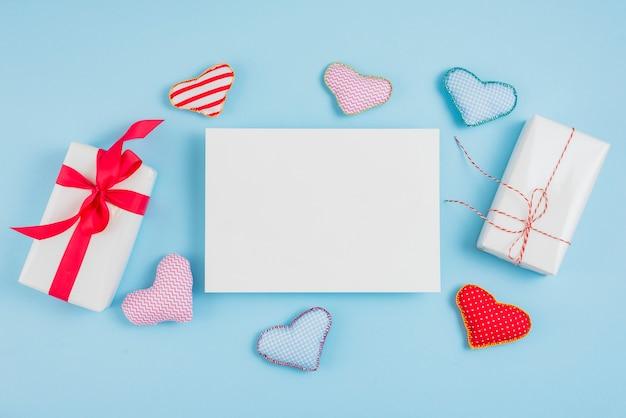 Подарочные коробки возле бумажных и игрушечных сердечек