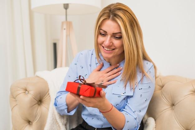 ソファのギフトボックスと若い幸せな驚いた女性