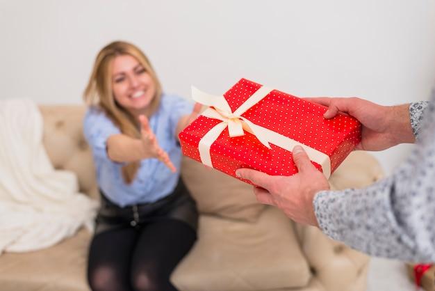 Парень дает подарок молодой улыбающейся леди на диване