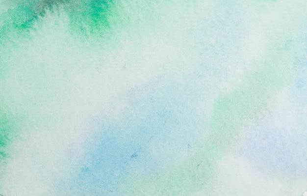 青色と緑色の半透明な染料のこぼれ