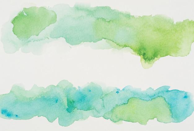 Лазурные и зеленые краски на белой бумаге