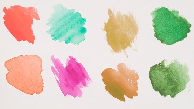 白い紙の茶色、緑色、アクアマリン、赤色、ピンク色の塗料の混合