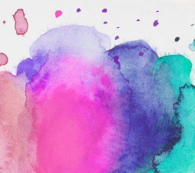 Розовая, голубая и аквамариновая смесь красок на белой бумаге